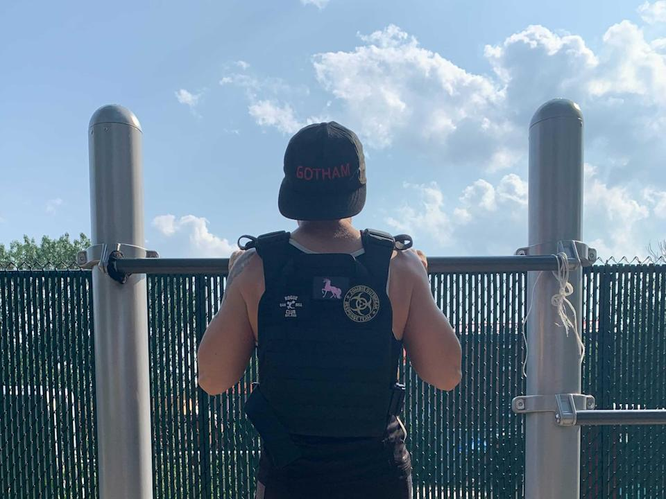 a sweaty fitness reporter at the top of a pull-up on a playground, wearing a weight vest