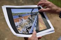Dennis Diggins shows images of debris removal after the 9/11 terrorist attacks on the World Trade Center, at the Fresh Kills landfill on Staten Island