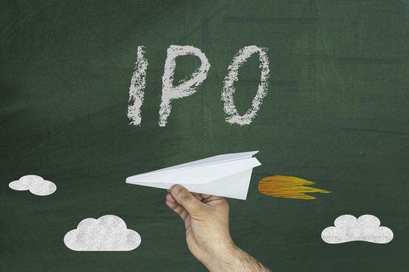 A hand holds a paper airplane in front of a chalkboard with the word IPO written on it.