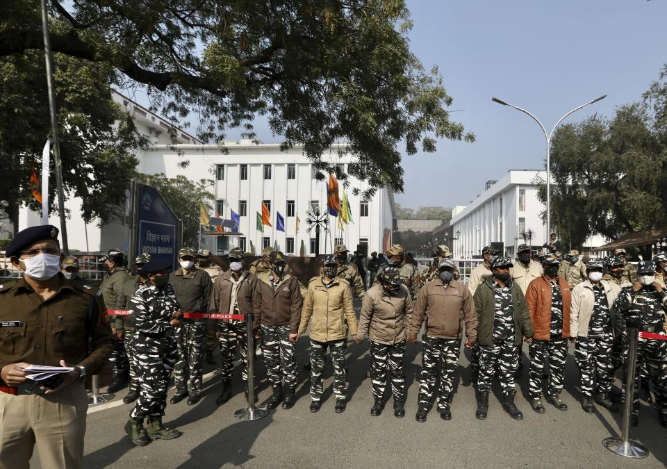 Security officers stand guard outside the venue where farmer leaders are meeting with government representatives in New Delhi, India, Wednesday, Dec. 30, 2020. Protesting farmers fear the government will stop buying grain at minimum guaranteed prices and corporations will then push down prices. The government says the three laws approved by Parliament in September will enable farmers to market their produce and boost production through private investment. (AP Photo/Manish Swarup)