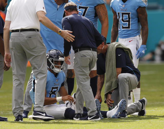 FILE - In this Sept. 9, 2018 file photo Tennessee Titans quarterback Marcus Mariota (8) is attended on the field, during the second half of an NFL football game against the Miami Dolphins in Miami Gardens, Fla. Mariota practiced fully Wednesday, Sept. 12, 2018 after being knocked out of Tennessees season opener after hurting the elbow on his throwing arm. (AP Photo/Brynn Anderson, file)