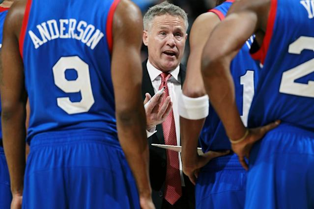 Philadelphia 76ers head coach Brett Brown, center, confers with players during a timeout against the Denver Nuggets in the fourth quarter of the Sixers' 114-102 victory in an NBA basketball game in Denver on Wednesday, Jan. 1, 2014. (AP Photo/David Zalubowski)