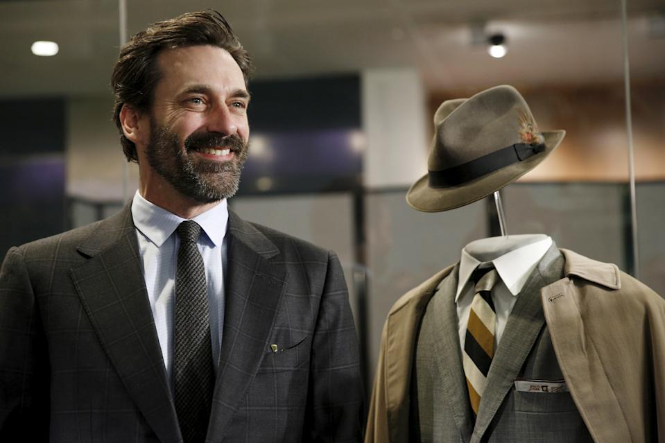 """""""Mad Men"""" star Jon Hamm stands beside the wardrobe he wore as the character """"Don Draper"""" during a donation ceremony at the Smithsonian National Museum of American History in Washington March 27, 2015. The museum accepted a donation of more than 50 artifacts from the AMC program """"Mad Men"""" to represent mid-century advertising history as part of their  """"American Enterprise"""" exhibition which opens this summer.  REUTERS/Kevin Lamarque"""