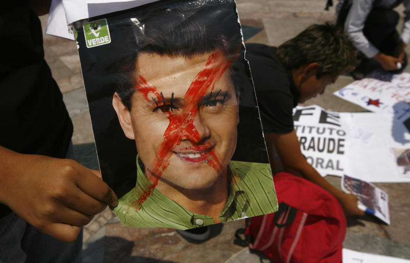 A man holds a defaced image of President-elect Enrique Pena Nieto as Mexicans unhappy with the presidential election results prepare for a march, in Mexico City, Saturday, July 7, 2012. The protestors marched in rejection of the final count in the presidential election showing the former ruling party candidate, Pena Nieto, as the victor. They believe the PRI engaged in vote-buying that illegally tilted millions of votes. PRI officials deny the charge. (AP Photo/Marco Ugarte)