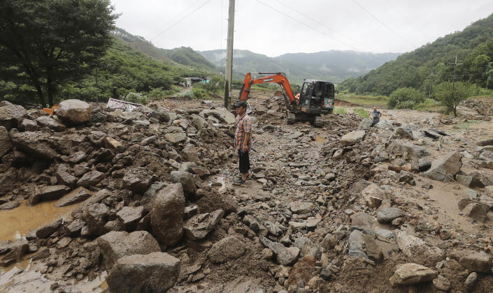 A man stands on road covered with mud and rocks after heavy rains in Chungju, South Korea, Sunday, Aug. 2, 2020. South Korean Meteorological Administration issued a warning of heavy rain for Seoul and central area. (Chun Kyung-hwan/Yonhap via AP)