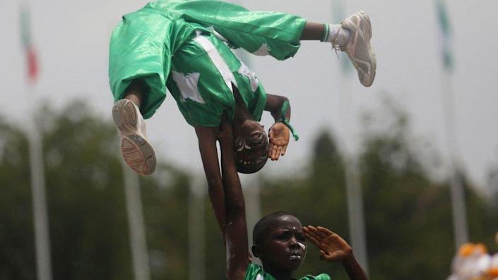 Two acrobatic boys performing in Abuja. They are wearing green and white outfits - the colours of the Nigerian flag - with stars on them. one boy is holding another with just one hand above his head. They are both saluting. They have white face paint on and a serious expression.