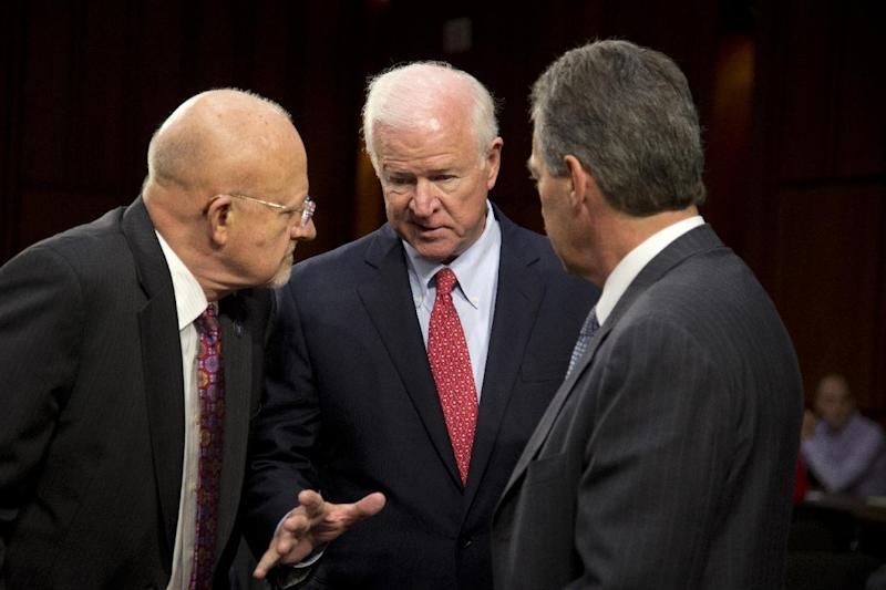 Senate Intelligence Committee Vice Chairman Sen. Saxby Chambliss, R-Ga.,center, talks with Director of National Intelligence James Clapper, left, and Deputy Attorney General James Cole on Capitol Hill in Washington, Thursday, Sept. 26, 2013, prior to the start of the Senate Intelligence Committee hearing on the Foreign Intelligence Surveillance Act (FISA), and National Security Agency (NSA) call records. Lawmakers who oversee US intelligence agencies are working to expand the government's spying powers to allow the FBI to immediately begin electronically monitoring terror suspects who travel to the United States and who already were under surveillance overseas by the NSA. (AP Photo/Carolyn Kaster)
