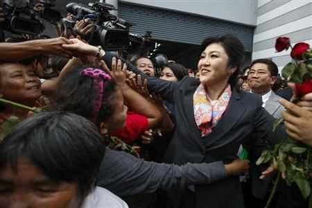 Thailand's Prime Minister Yingluck Shinawatra greets her supporters as she leaves the Permanent Secretary of Defence office in Bangkok