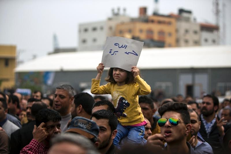 Palestinians, employed by the Palestinian Authority, chant slogans and wave placards during a demonstration against the decision to reduce their salaries in Gaza City on April 8, 2017