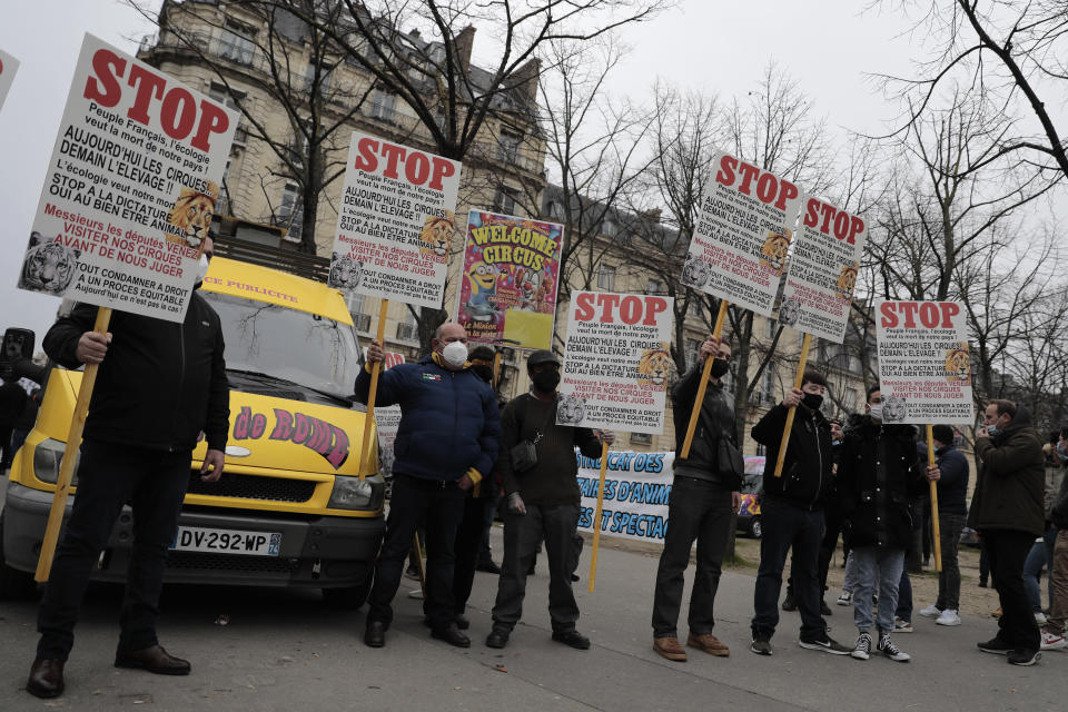 """Circus workers holds posters during a protest near the National Assembly, Tuesday, Jan.26, 2021. French lawmakers start debating Tuesday a bill that would ban using wild animals in traveling circuses and keeping dolphins and whales in captivity in marine parks, amid other measures to better protect animal welfare. Circus workers stage a protest outside the National Assembly to denounce what they consider """"a mistake."""" (AP Photo/Lewis Joly)"""