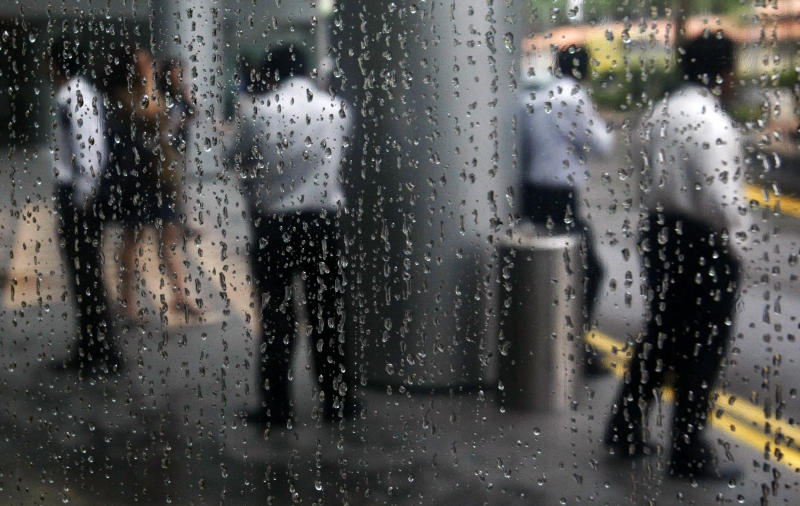 Office workers are reflected in a rain-covered window as they stand at the lobby of a building in Singapore's financial district March 16, 2009. Singapore's economy is expected to shrink 4.9 percent in 2009 from a year earlier, pushing the Singapore dollar down to 1.56 against the U.S. dollar at the end of the year, a central bank survey showed. REUTERS/Vivek Prakash (SINGAPORE BUSINESS ENVIRONMENT IMAGE OF THE DAY TOP PICTURE)