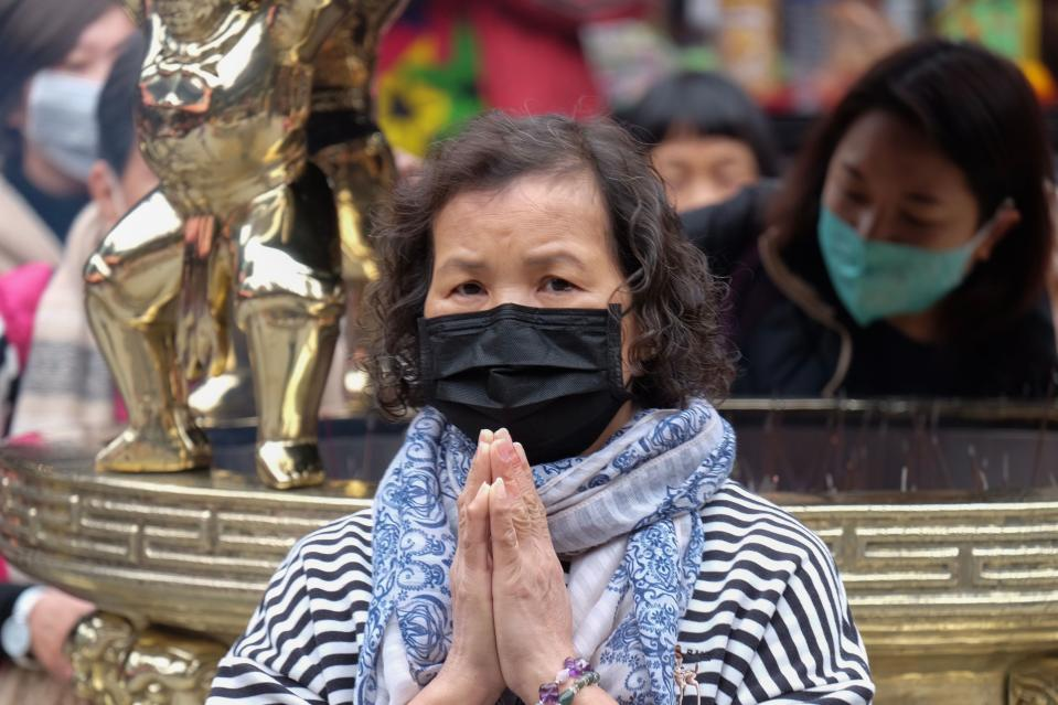 A woman wearing a protective mask prays at the Lungshan temple during the fourth day of the Lunar New year of the Rat in Taipei in January 28, 2020. - Taiwan has uncovered five cases of the deadly coronavirus so far, the latest a Taiwanese woman in her 50s who was working in Wuhan and flew to the island on January 20. The virus, which can cause a pneumonia-like acute respiratory infection, has in a matter of weeks killed more 106 people and infected more than 4,000 in China, while cases have been identified in more than a dozen other countries. (Photo by Sam Yeh / AFP) (Photo by SAM YEH/AFP via Getty Images)