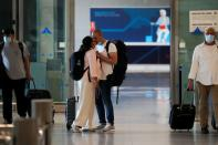 Tourist couple kiss as they arrive at Malaga-Costa del Sol Airport, in Malaga
