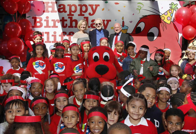 This image released by Scholastic shows first graders celebrating Clifford the Big Red Dog's 50th anniversary, along with his creator Norman Bridwell, center rear, his daughter Elizabeth, left, and Scholastic CEO Dick Robinson at Scholastic's headquarters in New York, Monday, Sept. 24, 2012. (AP Photo/Scholastic, Stuart Ramson)
