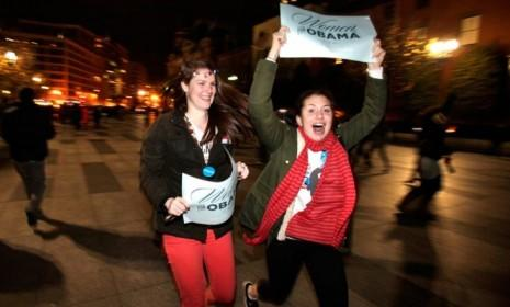 """Revelers holding signs that say """"Women for Obama"""" run through the streets after the election is called for the president."""