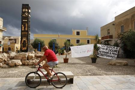 """A man cycles past banners, which read: """"An island full of pain that bears the indifference of the world"""" (R) and """"Lampedusa wants to welcome immigrants alive, not dead"""", in the centre of the southern Italian island of Lampedusa October 4, 2013. REUTERS/Antonio Parrinello"""