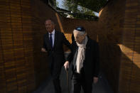 """A holocaust survivor walks along walls with name stones after King Willem-Alexander officially unveiled a new monument in the heart of Amsterdam's historic Jewish Quarter on Sunday, Sept. 19, 2021, honoring the 102,000 Dutch victims of the Holocaust. Designed by Polish-Jewish architect Daniel Libeskind, the memorial is made up of walls shaped to form four Hebrew letters spelling out a word that translates as """"In Memory Of."""" The walls are built using bricks each of which is inscribed with the name of one of the 102,000 Jews, Roma and Sinti who were murdered in Nazi concentration camps during World War II or who died on their way to the camps. (AP Photo/Peter Dejong)"""