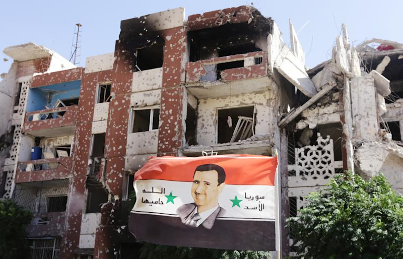 A flag showing Syrian President Bashar al-Assad flutters near damaged buildings in Adra northeast of the capital Damascus on September 25, 2014