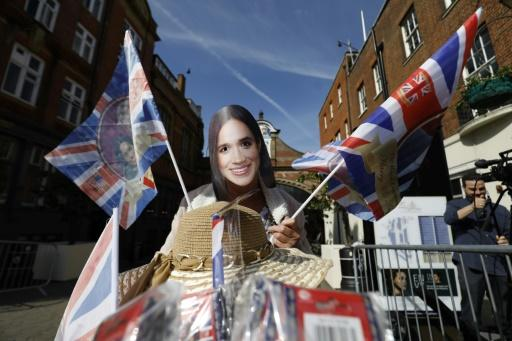 A woman selling flags featuring Britain's Prince Harry and US actress Meghan Markle near Windsor Castle in Windsor on May 18, 2018, the day before the Royal wedding