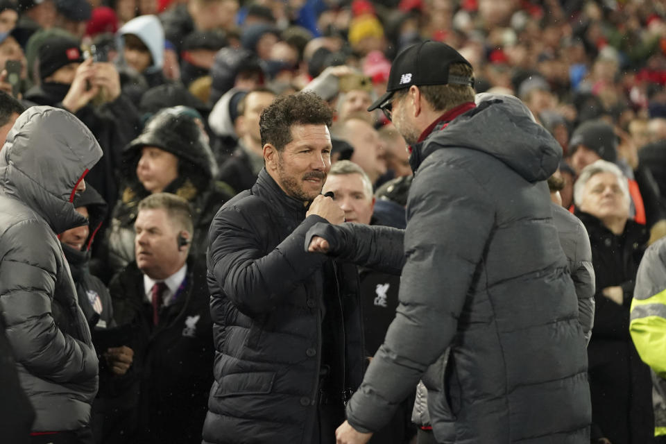 Atletico Madrid's head coach Diego Simone, left, and Liverpool's manager Jurgen Klopp greet each other prior a second leg, round of 16, Champions League soccer match between Liverpool and Atletico Madrid at Anfield stadium in Liverpool, England, Wednesday, March 11, 2020. (AP Photo/Jon Super)