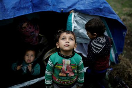 A Syrian refugee boy stands in front of his family tent at a makeshift camp for refugees and migrants next to the Moria camp on the island of Lesbos, Greece, November 30, 2017. REUTERS/Alkis Konstantinidis