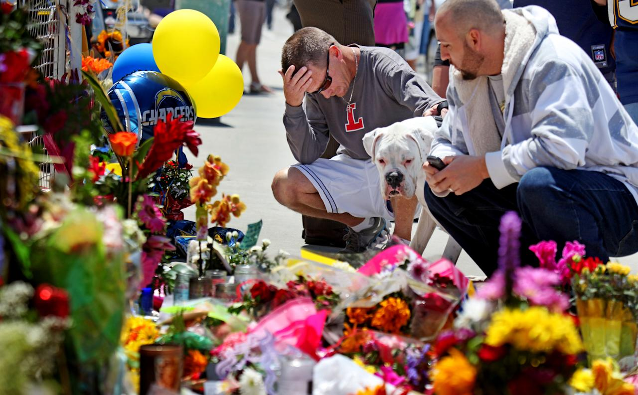 OCEANSIDE, CA - MAY 3: Ted Dalsey pays his respects with his dog Second Chance at a memorial outside of Junior Seau's beach home on April 3, 2012 in Oceanside, California. The former linebacker for the San Diego Chargers, Junior Seau, was found dead at his home on May 2, 2012. According to reports, Seau had died from a self-inflicted gun shot wound to the chest. (Photo by Sandy Huffaker/Getty Images)
