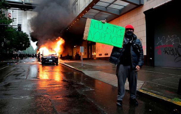 PHOTO: A man holds a sign in front of burning vehicles following demonstrations protesting the death of George Floyd, in Seattle, May 30, 2020. (Jason Redmond/AFP via Getty Images)