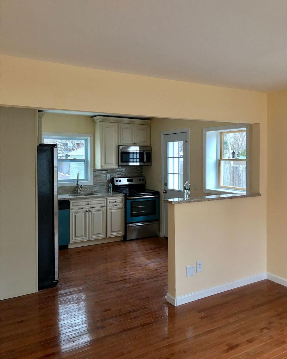 <p>The partial wall separating the living space from the kitchen makes this space feel more cramped than it needs to, while the darker stain of the wood floors makes it feel old and damp. </p>