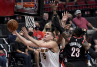 Denver Nuggets center Nikola Jokic, left, drives to the basket on Portland Trail Blazers forward Robert Covington, right, during the first half of Game 4 of an NBA basketball first-round playoff series in Portland, Ore., Thursday, May 29, 2021. (AP Photo/Steve Dykes)