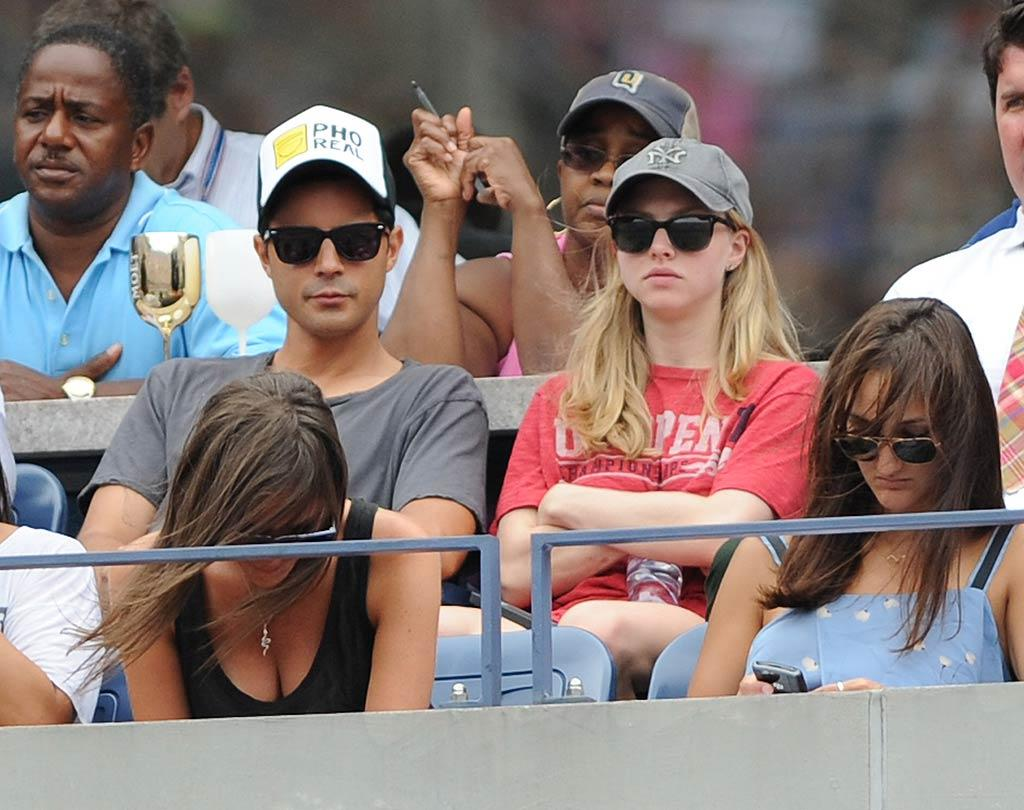 "Amanda Seyfried was also at the US Open looking a little more casual in a T-shirt, shorts, and a Yankees baseball cap. But who was the cute mystery man sitting next to her? Uri Schanker/<a href=""http://www.wireimage.com"" target=""new"">WireImage.com</a> - September 5, 2011"