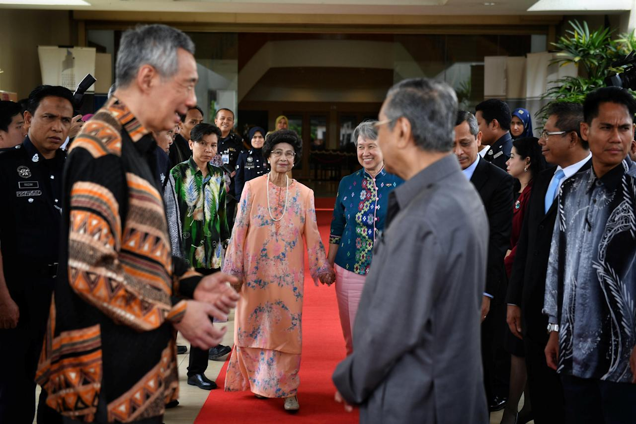 Siti Hasmah Mohd Ali, wife of Malaysian Prime Minister Mahathir Mohamad (front centre R), walks with Ho Ching, wife of Singapore's Prime Minister Lee Hsien Loong (front L), at the Perdana Leadership Foundation in Putrajaya, Malaysia 19 May 2018. Ariffin Jamar/The Straits Times via REUTERS ATTENTION EDITORS -  THIS IMAGE HAS BEEN SUPPLIED BY A THIRD PARTY.  NO RESALES. NO ARCHIVES.    SINGAPORE OUT.