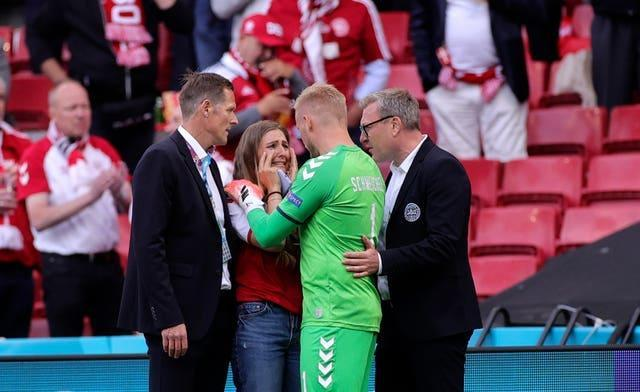 Kasper Schmeichel speaks to Christian Eriksen's wife Sabrina Kvist by the side of the pitch