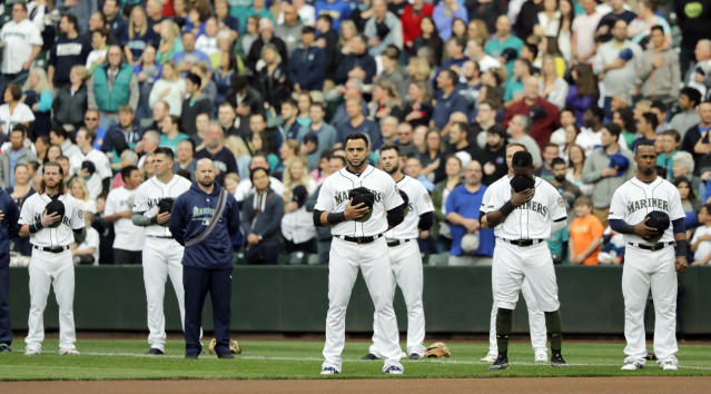 Seattle Mariners, including designated hitter Nelson Cruz, center, stand during the singing of the national anthem before the team's baseball game against the Minnesota Twins, Saturday, May 26, 2018, in Seattle. (AP Photo/Ted S. Warren)