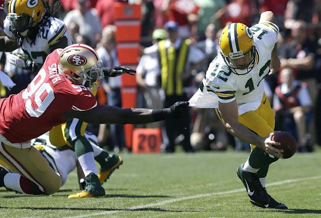 Green Bay Packers quarterback Aaron Rodgers (12) tries to run from San Francisco 49ers linebacker Aldon Smith (99) during the first quarter of an NFL football game, Sunday, Sept. 8, 2013, in San Francisco. Smith sacked Rodgers on the play. (AP Photo/Jeff Chiu)