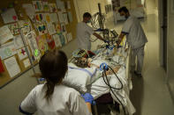 Medical staff wheel a bed with a COVID-19 patient into the intensive care ward of the Erasme hospital in Brussels, Wednesday, April 28, 2021. (AP Photo/Francisco Seco)
