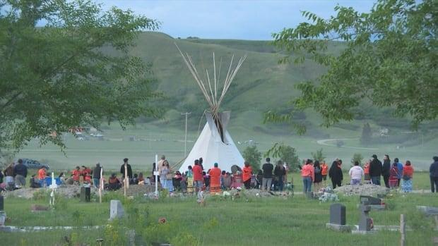 A large group of people gathered on the Cowessess First Nation in southeast Saskatchewan on Saturday night to honour those who were buried in what are believed to be 751 unmarked graves at the site of the former Marieval Indian Residential School. (Olivier Rouquairol Jodouin/CBC - image credit)