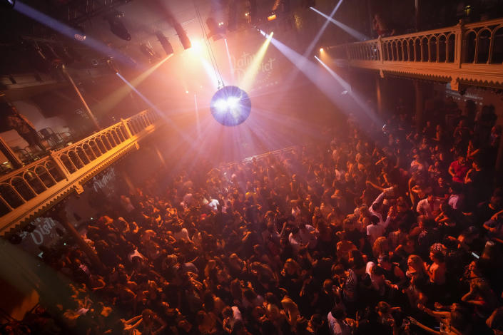 People dance in close proximity at Paradiso pop venue, club and cultural center, in Amsterdam, Saturday, Sept. 25, 2021, the day The Netherlands dropped the coronavirus related 1.5 meter (5 feet) rule. Paradiso is housed in a converted former church building that dates from the nineteenth century. (AP Photo/Peter Dejong)
