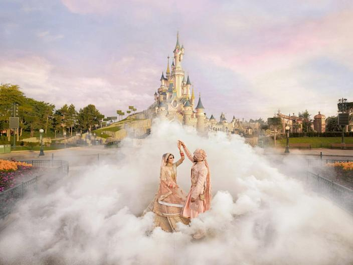 A groom twirls a bride surrounded by fog in front of Cinderella's castle at Disneyland Paris.