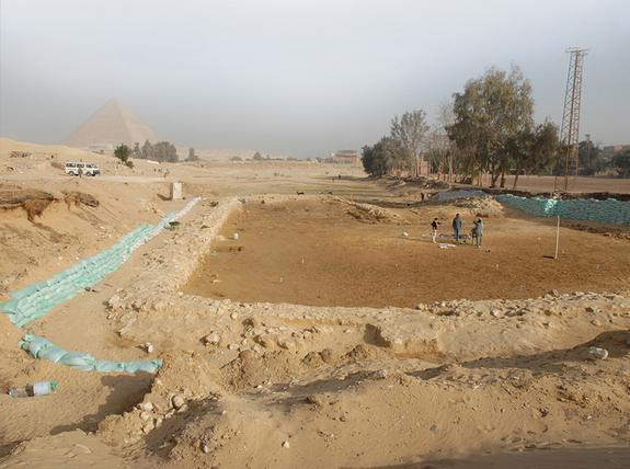 An image of the OK (Old Kingdom) Corral with the Giza pyramids in the distance. Researchers note that it was large enough to hold 55 cattle with feeding pens. There may also have been areas for slaughter.