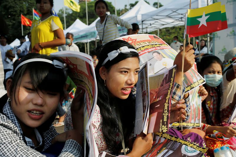 Participants carry Myanmar flags during a nationalist rally in Yangon