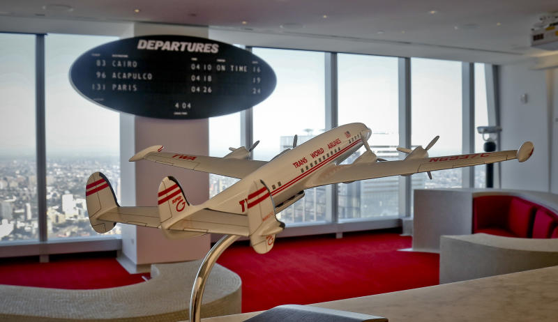 In this Oct. 4, 2017 photo, a model of a Lockheed Super Constellation and a vintage oval-shaped departure board showing flight numbers and destinations, are displayed at an installation at the company's retro meeting space at One World Trade Center in New York. A hotel under construction at the long-closed TWA Flight Center at New York's Kennedy Airport will conjure the glamour of air travel in 1962, when architect Eero Saarinen's jet-age landmark first opened. The $265 million hotel will have a rooftop pool and a museum stocked with artifacts, including uniforms lent by former TWA flight attendants. The TWA terminal closed in 2001, when TWA was acquired by American Airlines.(AP Photo/Bebeto Matthews)