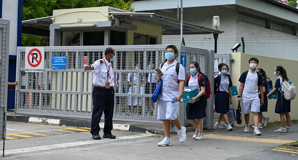 Students leave the River Valley High School compounds in Singapore after a 13-year-old boy was found dead on the premises with multiple wounds.
