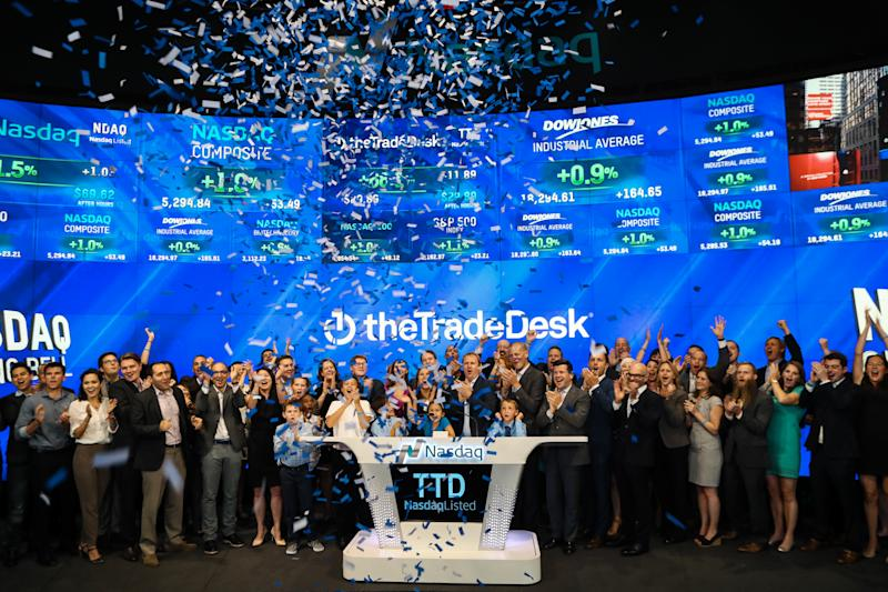 A group of people at the NASDAQ with confetti falling and The Trade Desk logo on the wall behind them.