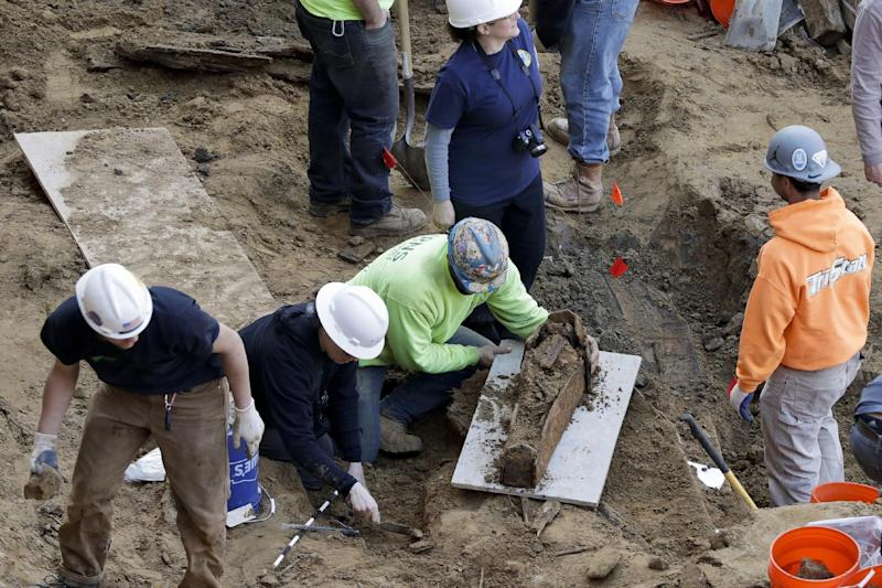 Workers excavate a coffin from a construction site in the Old City neighborhood, Thursday, March 9, 2017, in Philadelphia. Crews working on an apartment building in Philadelphia's historic district got a shock last month when their backhoes started hitting coffins and unearthing fully intact human remains. The site was supposed to be a former burial ground from 1707, and all remains were supposedly exhumed in the 1800s and moved to a different cemetery. (AP Photo/Matt Slocum)