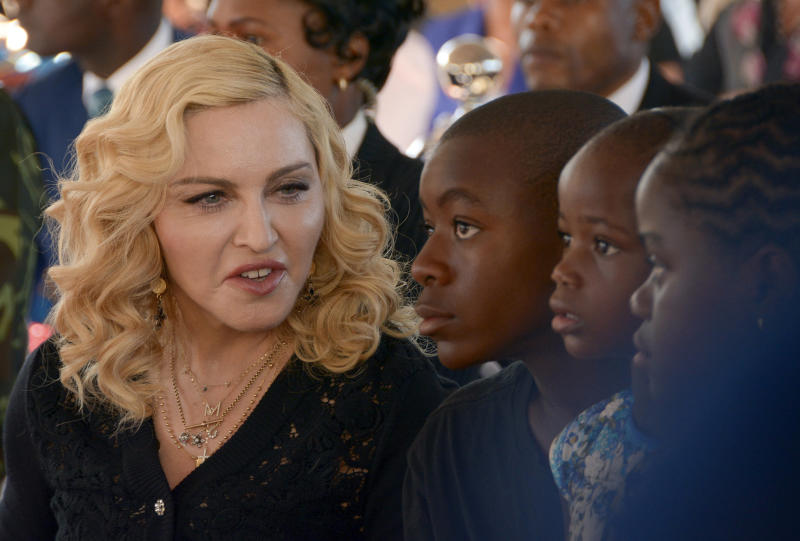 FILE- In this July 11, 2017 file photo, Madonna, left, sits with her adopted children David, Stella and Mercy, at the opening of The Mercy James Institute for Pediatric Surgery and Intensive Care, located at the Queen Elizabeth Central Hospital in the city of Blantyre, Malawi. A New York judge on Tuesday, July 18, 2017, has stopped an impending auction of pop star Madonna's personal items, including a love letter from her former boyfriend, the late rapper Tupac Shakur, a pair of worn panties and a hairbrush containing strands of her hair. (AP Photo Thoko Chikondi, File)