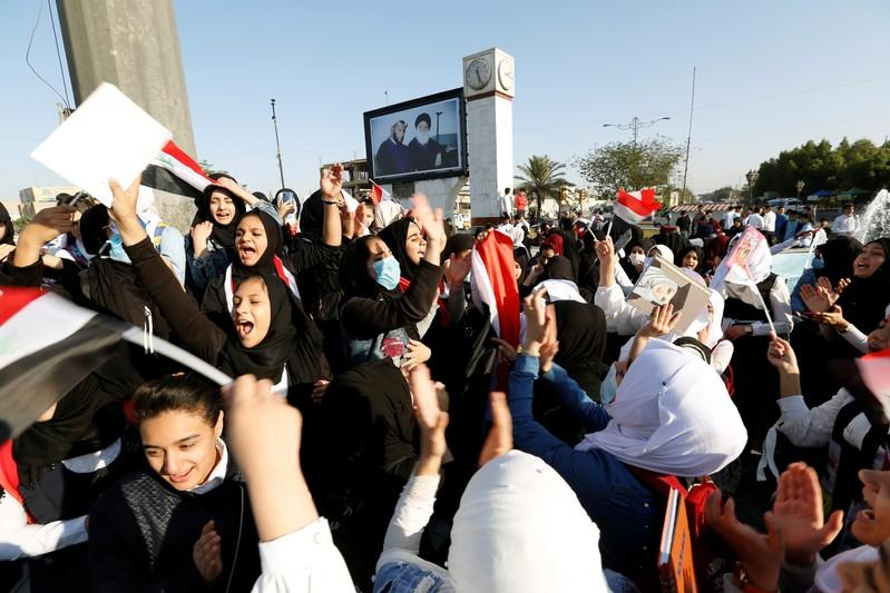 School students chant slogans as they take part in ongoing anti-government protests in Baghdad