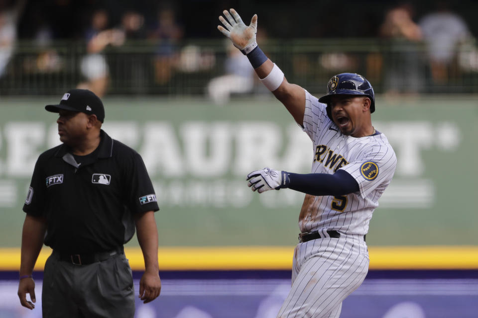 Milwaukee Brewers' Eduardo Escobar, right, reacts after hitting a two-RBI single during the second inning of a baseball game against the New York Mets, Sunday, Sept. 26, 2021, in Milwaukee. Escobar advanced to second base on a throwing error. (AP Photo/Aaron Gash)