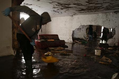 A man sweeps muddy water out of a flooded home after extreme rainfall due to Cyclone Cleopatra in Olbia on Sardinia island November 20, 2013. REUTERS/Tony Gentile