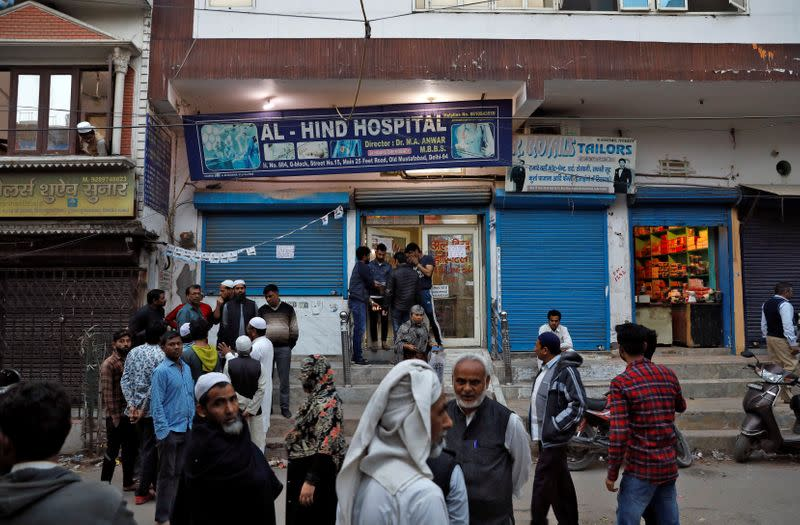 People gather outside the Al Hind hospital, where victims are treated and many have taken shelter after they fled their homes following clashes between people demonstrating for and against a new citizenship law in a riot affected area in New Delhi