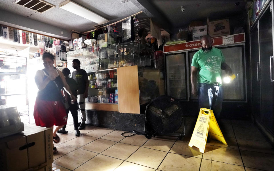 Keith, right, uses a flashlight to help others shop in the dark at a convenience store after the effects the effects of Hurricane Ida knocked out power in the area, Monday, Aug. 30, 2021, in New Orleans, La. (AP Photo/Eric Gay)